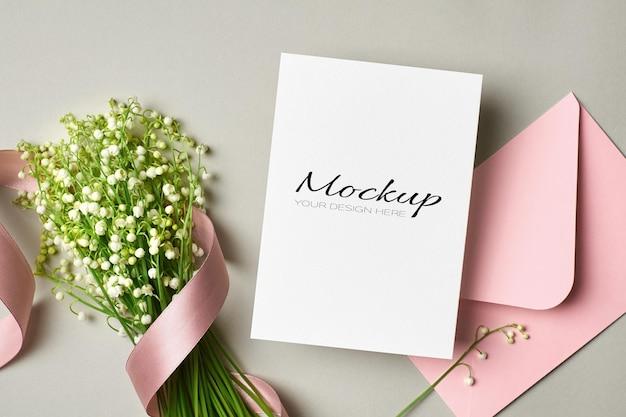 Makieta zaproszenia lub karty z pozdrowieniami z różową kopertą i bukietem kwiatów konwalii ze wstążką