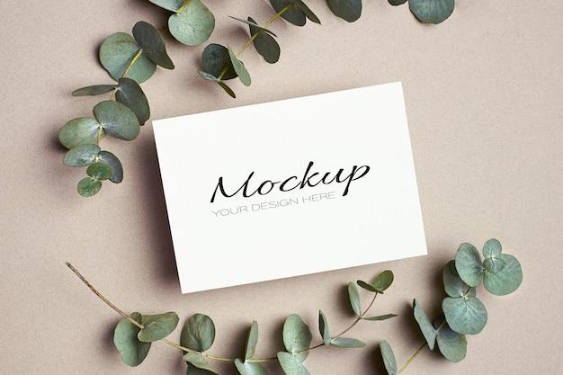 Makieta zaproszenia lub karty z pozdrowieniami z zielonymi gałązkami eukaliptusa