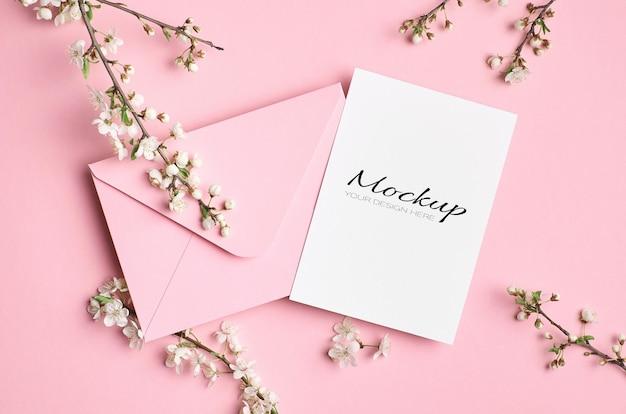 Makieta zaproszenia ślubne z kopertą i wiosennymi gałązkami drzewa z kwiatami