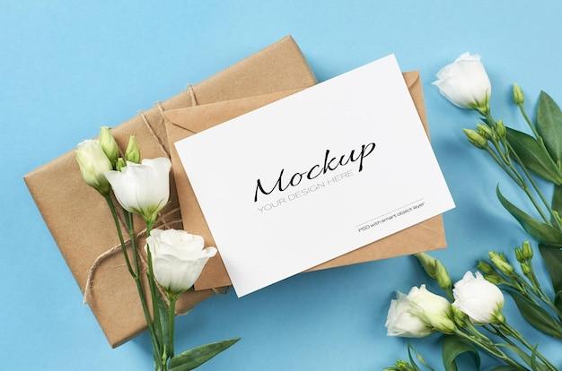 Makieta zaproszenia z białymi kwiatami eustoma i pudełkiem na niebieskim tle