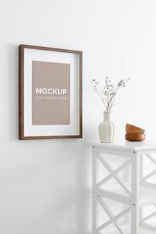 Makieta zdjęcia portretowego lub ramki graficznej na białej ścianie i meblach z suchymi roślinami w wazonie