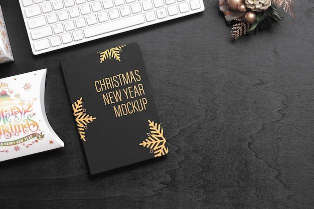 Makieta zeszytu w czarnej okładce na czarnym drewnie na boże narodzenie i nowy rok