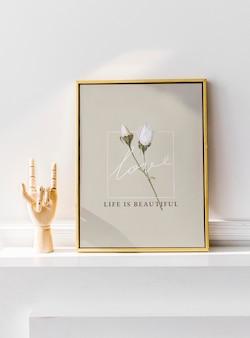Makieta złotej ramki na białej ścianie