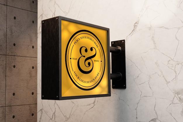 Makieta znaku logo na białej marmurowej ścianie