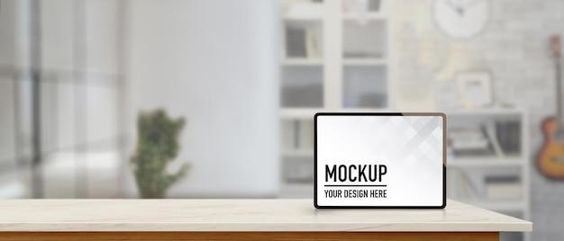 Makiety cyfrowego tabletu na marmurowym blacie z miejscem na kopię w niewyraźnym tle salonu