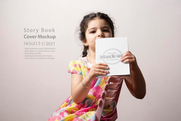 Mała dziewczynka czytająca nowatorską książkę z pustą okładką przed ciałem, edytowalna seria makiet psd z szablonem warstw inteligentnych obiektów gotowych do projektowania