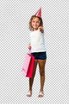 Mała dziewczynka na przyjęcie urodzinowe trzyma torbę z pamiątkami wskazuje palcem na ciebie