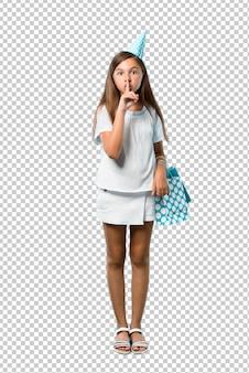 Mała dziewczynka przy przyjęciem urodzinowym trzyma prezent torbę pokazuje znaka końcowy usta