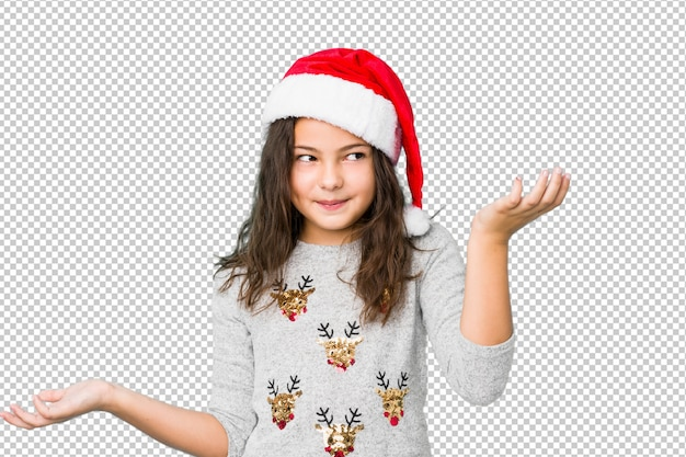 Mała dziewczynka świętuje boże narodzenie dzień wątpi ramiona w przesłuchanie gescie i wzrusza ramionami.