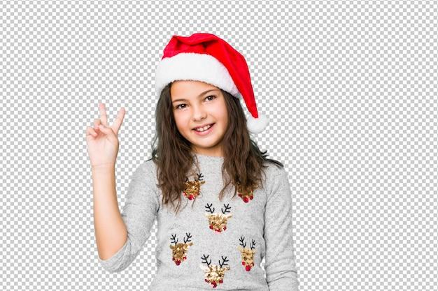 Mała dziewczynka świętuje dzień bożego narodzenia radosnego i beztroskiego pokazuje symbol pokoju z palcami.