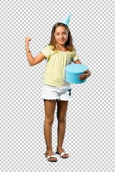 Mała dziewczynka trzyma prezent świętuje zwycięstwo przy przyjęciem urodzinowym