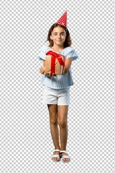 Mała dziewczynka trzyma prezent trzyma rękę krzyżować przy przyjęciem urodzinowym