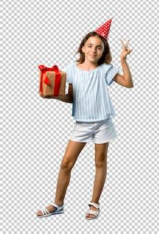 Mała dziewczynka trzyma prezent uśmiecha się zwycięstwo znaka i pokazuje przy przyjęciem urodzinowym