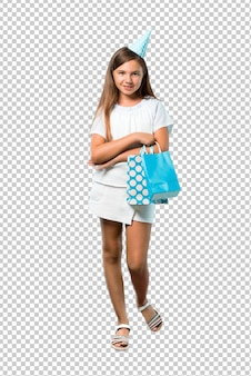 Mała dziewczynka trzymając torbę na prezent urodzinowy trzymając ręce skrzyżowane