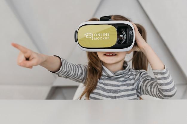 Mała dziewczynka wskazuje wskazując zestaw słuchawkowy wirtualnej rzeczywistości