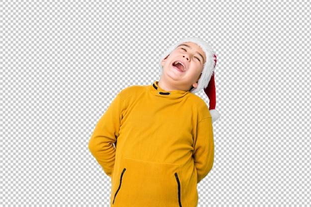 Mały chłopiec obchodzi boże narodzenie w kapeluszu santa zrelaksowany i szczęśliwy śmiejąc się, szyja rozciągnięta pokazując zęby.