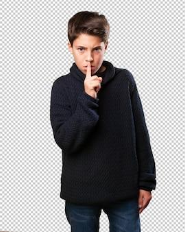Mały chłopiec robi gest ciszy