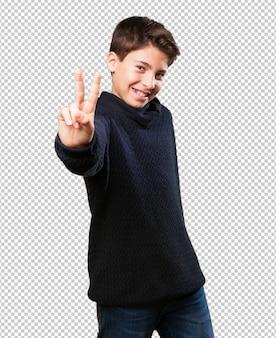 Mały chłopiec robi symbol zwycięstwa
