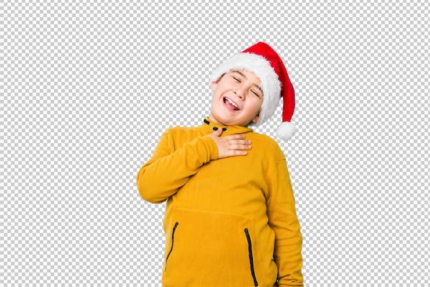 Mały chłopiec świętuje boże narodzenie w kapeluszu santa śmieje się głośno, trzymając rękę na piersi.