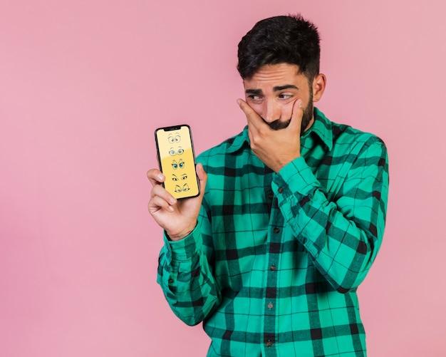 Martwi się młody człowiek trzyma telefon komórkowy makiety