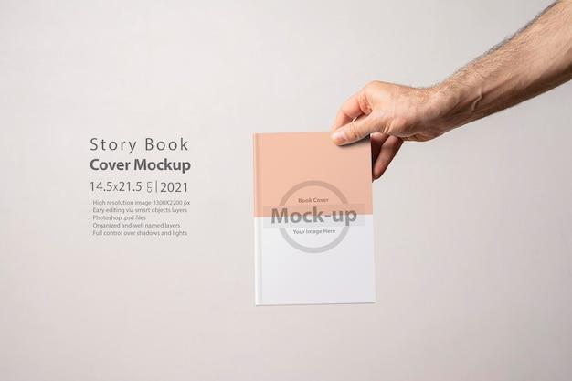 Męska ręka trzymająca zamknięty katalog książek z pustą okładką edytowalną serią makiet z warstwami obiektów inteligentnych