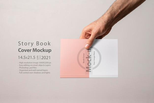 Męska ręka z makietą okładki katalogu zamkniętej książki
