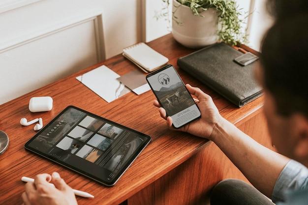 Męski bloger korzystający z makiety telefonu komórkowego