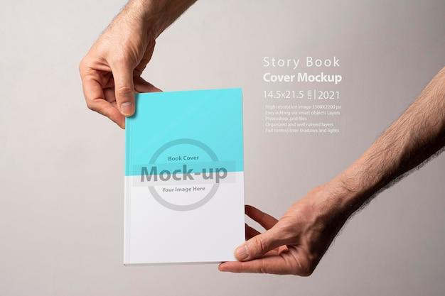 Męskiej ręki trzymającej zamknięty katalog książek z pustą okładką