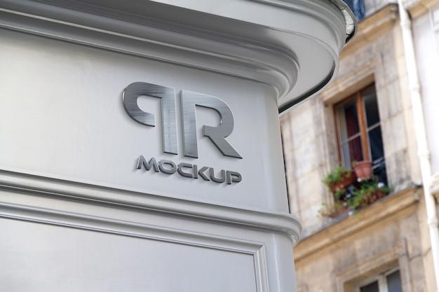 Metaliczne logo na rogu sklepu na makiecie ulicznej