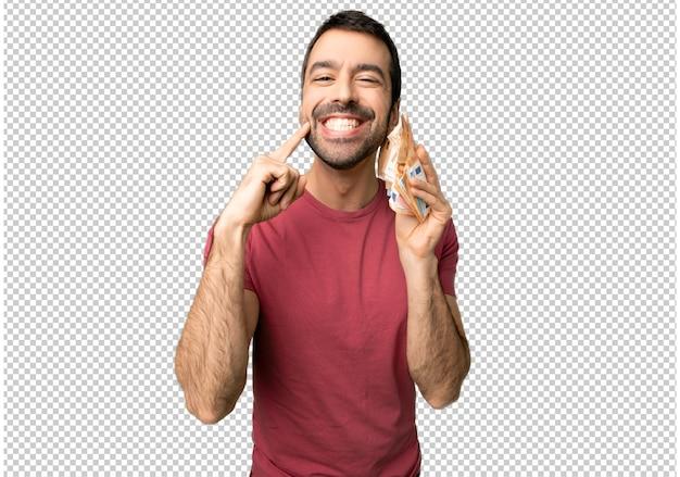 Mężczyzna biorąc dużo pieniędzy uśmiecha się z wyrażeniem szczęśliwy i przyjemny