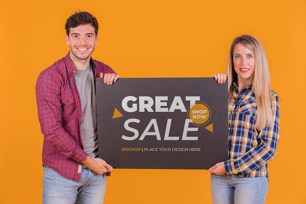 Mężczyzna i kobieta trzyma makietę koncepcji znaku