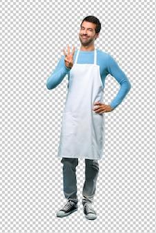 Mężczyzna jest ubranym fartucha szczęśliwego i liczy trzy z palcami