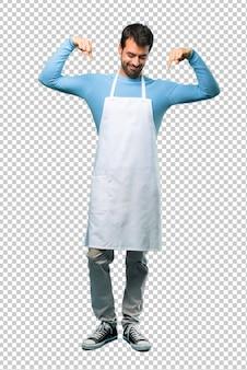 Mężczyzna jest ubranym fartucha wskazuje w dół z palcami