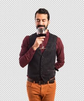Mężczyzna jest ubranym kamizelkę trzyma wino szkła