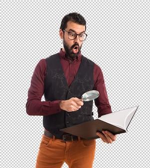 Mężczyzna jest ubranym kamizelkę z powiększać - szkło