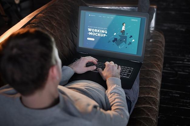 Mężczyzna na kanapie pracuje z domu na laptopie
