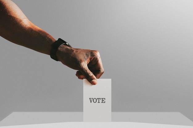 Mężczyzna oddający swój głos na makietę urny wyborczej