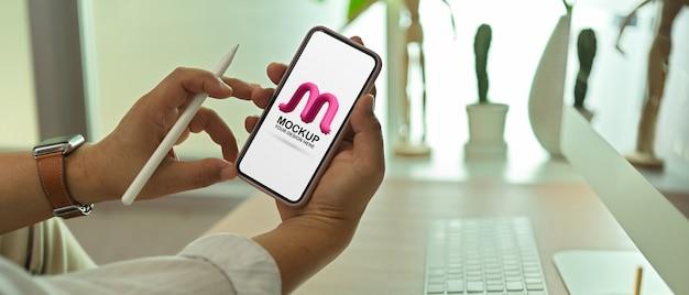 Mężczyzna przedsiębiorca pokazuje makieta ekranu smartfona na miejscu pracy