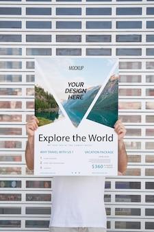 Mężczyzna przedstawia plakatowego mockup przed bramą