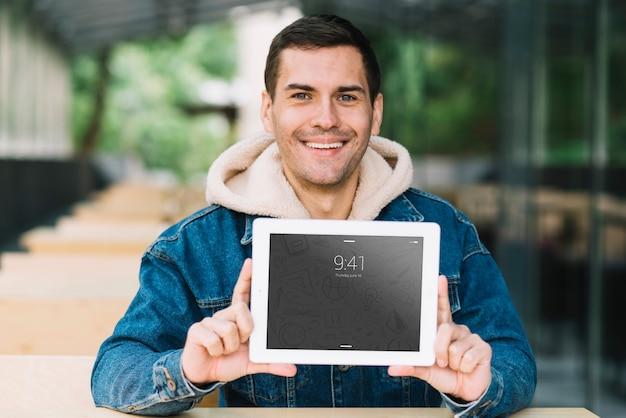 Mężczyzna przedstawia tablet makieta