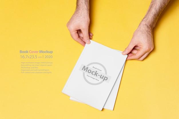 Mężczyzna ręka trzyma katalog zamkniętej książki na białym tle