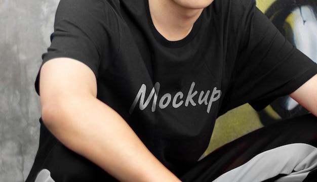 Mężczyzna siedzący nosić makieta czarnej koszuli