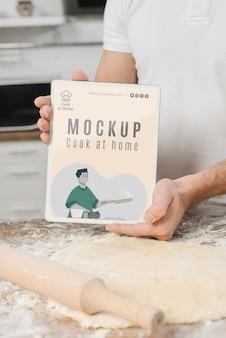 Mężczyzna trzyma książkę podczas toczenia ciasta w kuchni