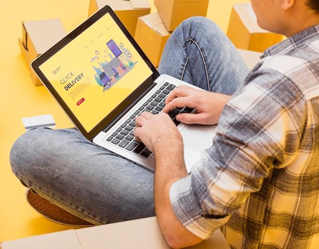 Mężczyzna trzyma laptopa makiety wokół paczek