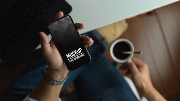 Mężczyzna trzyma makieta smartfona podczas picia kawy w obszarze roboczym