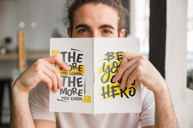 Mężczyzna trzyma makietę okładki książki przed twarzą