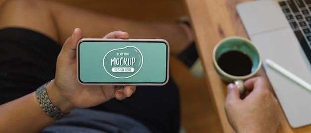 Mężczyzna trzyma makiety poziomego smartfona i filiżanki kawy, relaksując się siedząc w miejscu pracy