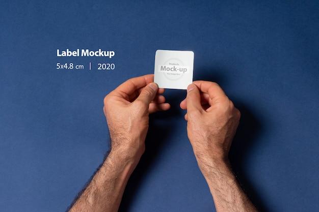 Mężczyzna trzyma małą makietę etykiety przed ciemnoniebieską powierzchnią