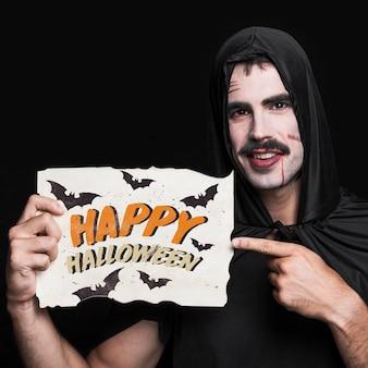 Mężczyzna trzyma papier z halloween literowaniem
