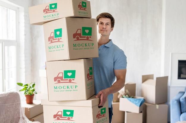 Mężczyzna trzyma pudełka z przedmiotami w swoim nowym domu